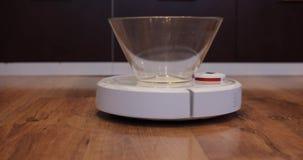 Η ηλεκτρική σκούπα ρομπότ φέρνει το κενό πιάτο των γλυκών από τα δεξιά  φιλμ μικρού μήκους