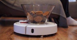 Η ηλεκτρική σκούπα ρομπότ φέρνει το πιάτο των γλυκών στον ιδιοκτήτη της απόθεμα βίντεο