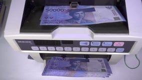 Η ηλεκτρονική αντίθετη μηχανή χρημάτων μετρά τη ρουπία της Ινδονησίας, σε αργή κίνηση φιλμ μικρού μήκους