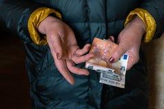 Η ηλικιωμένη ανώτερη γυναίκα κρατά τα ΕΥΡΟ- τραπεζογραμμάτια - ανατολικο-ευρωπαϊκή σύνταξη μισθών στοκ εικόνα