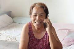 Η ηλικιωμένη ασιατική γυναίκα καλεί το κινητό τηλέφωνο στοκ εικόνα