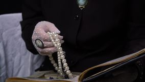 Η ηλικιωμένη γυναίκα ανοίγει την κρύπτη βιβλίων της και κρατά το κόσμημά της απόθεμα βίντεο