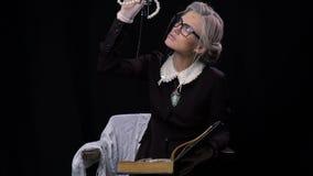 Η ηλικιωμένη γυναίκα ανοίγει το βιβλίο όπου έχει ένα stash με το κόσμημα φιλμ μικρού μήκους