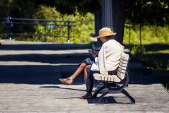 Η ηλικιωμένη γυναίκα αφροαμερικάνων κάθεται στον ξύλινο πάγκο σε ένα πάρκο και κοιτάζει βιαστικά το smartphone της στοκ εικόνες με δικαίωμα ελεύθερης χρήσης
