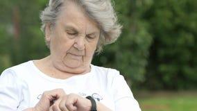 Η ηλικιωμένη γυναίκα εξετάζει έναν ιχνηλάτη ικανότητας wristband φιλμ μικρού μήκους