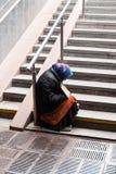 Η ηλικιωμένη γυναίκα επαιτών κάθεται στα σκαλοπάτια στοκ εικόνα