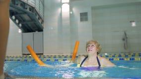 Η ηλικιωμένη γυναίκα επαναλαμβάνει τις ασκήσεις εκπαιδευτών ` s στην πισίνα απόθεμα βίντεο
