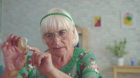 Η ηλικιωμένη γυναίκα κρατά και εξετάζει μια συνεδρίαση ενίσχυσης ακρόασης φιλμ μικρού μήκους