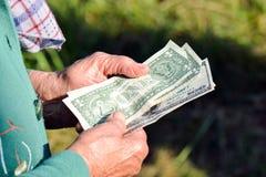 Η ηλικιωμένη γυναίκα κρατά τα χρήματα στα χέρια της Μια ηλικιωμένη γυναίκα με τα δολάρια στα χέρια της Ελεημοσύνες ένδειας Στοκ Εικόνες