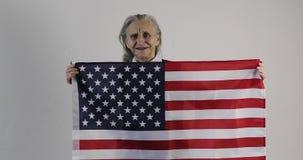 Η ηλικιωμένη γυναίκα με τις ρυτίδες στέκεται και κρατά τη αμερικανική σημαία στο άσπρο υπόβαθρο απόθεμα βίντεο