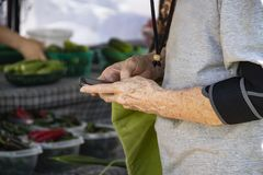 Η ηλικιωμένη γυναίκα με το στήριγμα βραχιόνων και το κύτταρο τηλεφωνούν στην αγορά αγροτών - κινηματογράφηση σε πρώτο πλάνο και ε στοκ εικόνα