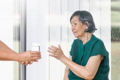 Η ηλικιωμένη γυναίκα παίρνει ένα ποτήρι του νερού από το caregiver στοκ εικόνες με δικαίωμα ελεύθερης χρήσης
