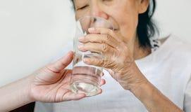 Η ηλικιωμένη γυναίκα παίρνει ένα ποτήρι του νερού από το caregiver στοκ φωτογραφίες με δικαίωμα ελεύθερης χρήσης