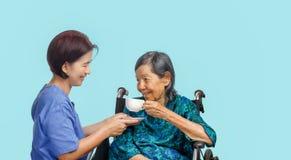Η ηλικιωμένη γυναίκα παίρνει μια φλυτζάνα τσαγιού από το caregiver στοκ φωτογραφία