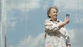 Η ηλικιωμένη γυναίκα παίρνει τις φωτογραφίες χρησιμοποιώντας το ασημένιο smartphone φιλμ μικρού μήκους