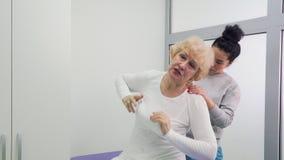 Η ηλικιωμένη γυναίκα παραπονιέται για τον πόνο στο χαμηλότερο πίσω σε έναν γιατρό φιλμ μικρού μήκους