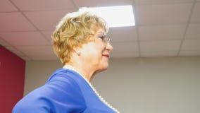 Η ηλικιωμένη γυναίκα περπατά το διάδρομο στο φόρεμα κατά τη διάρκεια μ φιλμ μικρού μήκους