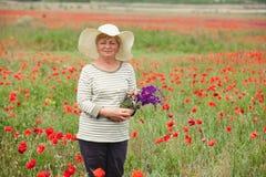 Η ηλικιωμένη γυναίκα σε ένα λιβάδι με τις παπαρούνες Στοκ φωτογραφία με δικαίωμα ελεύθερης χρήσης