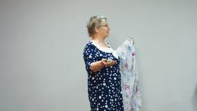 Η ηλικιωμένη γυναίκα στο μπλε φόρεμα διοργανώνει μια παρουσίαση αρώμα φιλμ μικρού μήκους