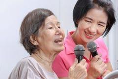 Η ηλικιωμένη γυναίκα τραγουδά ένα τραγούδι με την κόρη Στοκ Φωτογραφία