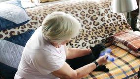 Η ηλικιωμένη γυναίκα φροντίζει μια γάτα φιλμ μικρού μήκους