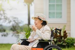 Η ηλικιωμένη γυναίκα χαλαρώνει στο κατώφλι Στοκ Φωτογραφία