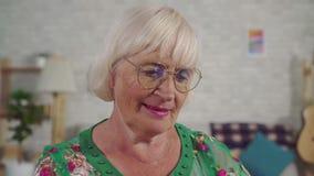 Η ηλικιωμένη γυναίκα χρησιμοποιεί ένα lap-top καθμένος στο καθιστικό κοντά επάνω απόθεμα βίντεο