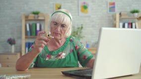 Η ηλικιωμένη γυναίκα ψάχνει τις πληροφορίες για μια ενίσχυση ακρόασης σε ένα lap-top φιλμ μικρού μήκους