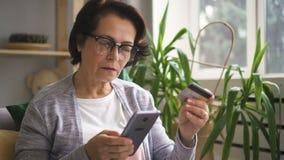 Η ηλικιωμένη γυναίκα ψωνίζει στο σε απευθείας σύνδεση κατάστημα, χρησιμοποιώντας το τηλέφωνο και την τραπεζική κάρτα απόθεμα βίντεο