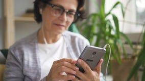 Η ηλικιωμένη χαμογελώντας γυναίκα είναι μουσική ακούσματος που χρησιμοποιεί το smartphone στο εγχώριο εσωτερικό απόθεμα βίντεο