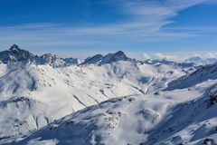 Η ηλιοφάνεια βουνών κορυφών καλύπτει τα ίχνη στο χιόνι στοκ φωτογραφίες