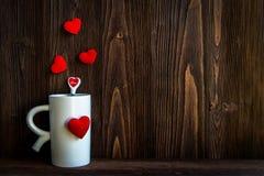 Η ημέρα βαλεντίνων με τον κόκκινο καφέ φλυτζανιών έραψε τα σύνορα σειρών καρδιών μαξιλαριών, παλαιό ξύλινο υπόβαθρο, Στοκ Εικόνες