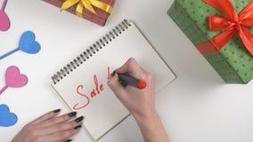 Η ημέρα βαλεντίνων ` s, απεικόνιση, χέρι γυναικών ` s γράφει σε ένα σημειωματάριο, πώληση 40 τοις εκατό από 60 fps απόθεμα βίντεο