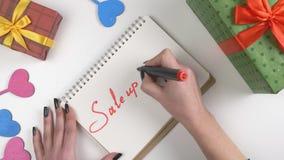 Η ημέρα βαλεντίνων ` s, απεικόνιση, χέρι γυναικών ` s γράφει σε ένα σημειωματάριο, πώληση μέχρι 50 τοις εκατό 60 fps απόθεμα βίντεο