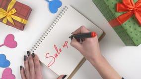 Η ημέρα βαλεντίνων ` s, απεικόνιση, χέρι γυναικών ` s γράφει σε ένα σημειωματάριο, πώληση μέχρι 70 τοις εκατό 60 fps απόθεμα βίντεο