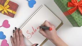 Η ημέρα βαλεντίνων ` s, απεικόνιση, χέρι γυναικών ` s γράφει σε ένα σημειωματάριο, πώληση μέχρι 60 τοις εκατό 60 fps απόθεμα βίντεο