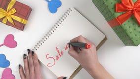 Η ημέρα βαλεντίνων ` s, απεικόνιση, χέρι γυναικών ` s γράφει σε ένα σημειωματάριο, πώληση μέχρι 65 τοις εκατό 60 fps απόθεμα βίντεο