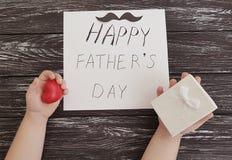 Η ημέρα πατέρων ` s, χέρια μωρών ` s, συγχαρητήρια γιορτάζει την παρούσα κόκκινη καρδιά σε ένα μαύρο ξύλινο υπόβαθρο στοκ εικόνες