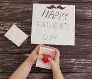Η ημέρα πατέρων ` s, χέρια μωρών ` s, συγχαρητήρια φιλίας γιορτάζει την παρούσα κόκκινη καρδιά σε ένα μαύρο ξύλινο υπόβαθρο στοκ εικόνα με δικαίωμα ελεύθερης χρήσης