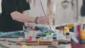 Η δημιουργική γυναίκα κάνει ένα στρέθιμο της προσοχής στο ύφασμα, χρησιμοποιώντας τα ακρυλικά χρώματα απόθεμα βίντεο
