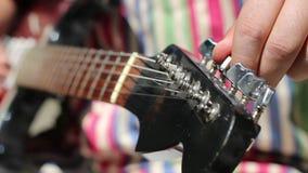 Η ηλεκτρική κιθάρα συντονίζει με το χέρι επάνω απόθεμα βίντεο