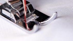 Η ηλεκτρική ράβοντας μηχανή κάνει ένα κόκκινο νήμα να ράψει κλείστε επάνω απόθεμα βίντεο