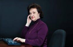 Η ηλικίας γυναίκα μπροστά από ένα όργανο ελέγχου που μιλά στα τηλέφωνα κυττάρων Στοκ εικόνα με δικαίωμα ελεύθερης χρήσης