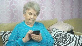 Η ηλικίας γυναίκα που χρησιμοποιεί ένα κινητό τηλέφωνο κάθεται σε έναν καναπέ απόθεμα βίντεο