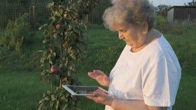 Η ηλικίας δεκαετία του '80 γυναικών που κρατά μια ψηφιακή ταμπλέτα υπαίθρια φιλμ μικρού μήκους