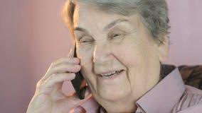 Η ηλικίας δεκαετία του '80 γυναικών που χαμογελά τις συζητήσεις στο κινητό τηλέφωνο φιλμ μικρού μήκους