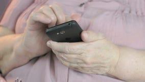 Η ηλικιωμένη γυναίκα δακτυλογραφεί το κείμενο σε ένα κινητό τηλέφωνο απόθεμα βίντεο