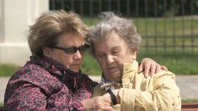 Η ηλικιωμένη γυναίκα εξετάζει τον ιχνηλάτη ικανότητας wristband απόθεμα βίντεο