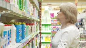 Η ηλικιωμένη γυναίκα επιλέγει τις χημικές καθαρίζοντας προμήθειες στην υπεραγορά Αγορές στο κατάστημα Ανώτερο θηλυκό προσεκτικά απόθεμα βίντεο