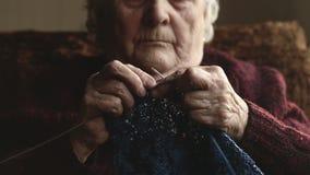 Η ηλικιωμένη γυναίκα κάθεται στο σπίτι και πλέκει τα ενδύματα απόθεμα βίντεο